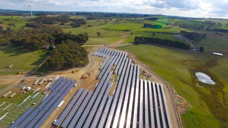 This is an aerial photograph of the Gullen Range solar farm that was being completed by Monford Group. The huge farm and large panels are in the middle of a big green field with rolling hills in the background.