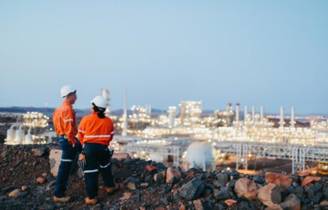This is a photograph of two workers in PPE at an observation point overlooking the Pluto LNG Plant.