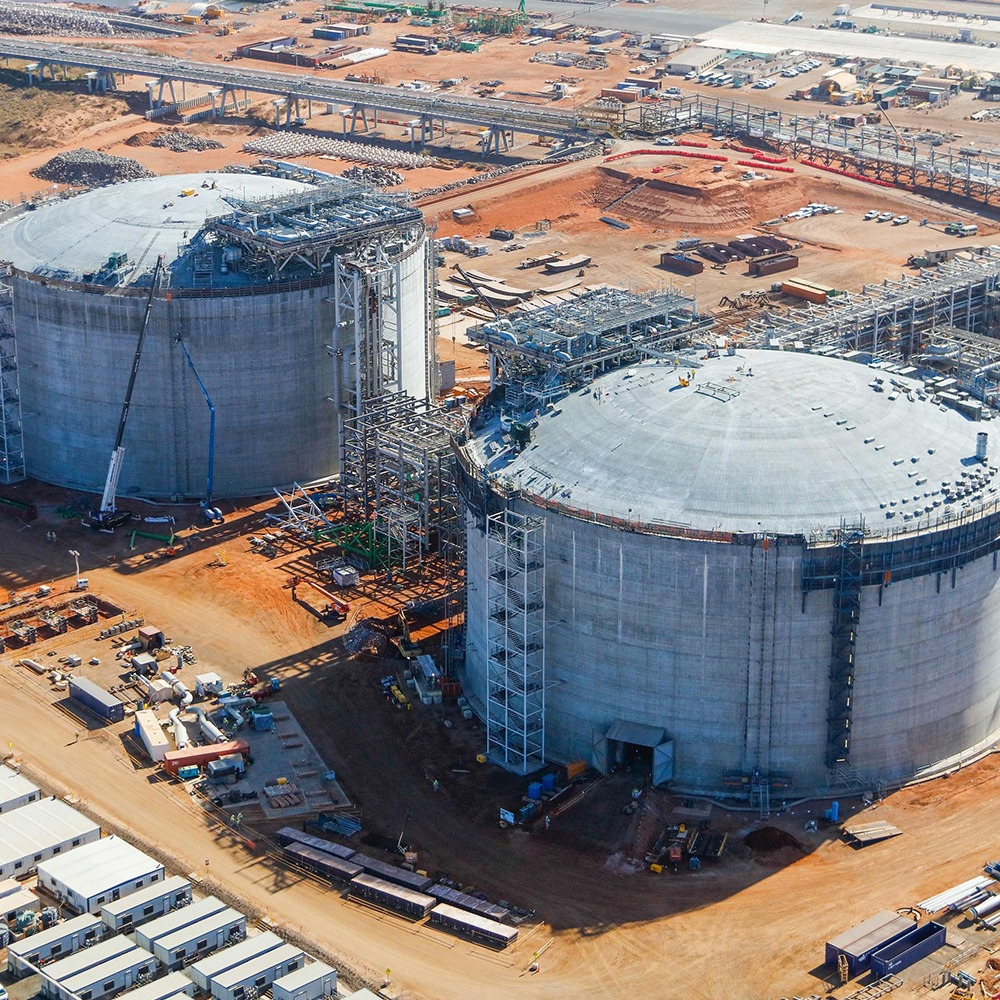 This is an aerial photograph of the Wheatstone Liquefied Natural Gas Plant, focused on the two large tanks surrounded by containers, portastations, and scaffolding.