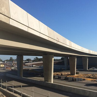 The photograph is of a newly built cement overpass completed by Monford that stretches across the freeway.