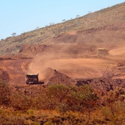 This photograph is of two large mining specific trucks descending into the main mining pit to be loaded with ore. The red dust from the trucks dissipates over the landscape.